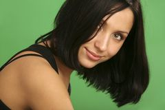 Flirty smile. Beautiful smiling brunette girl on the green background Royalty Free Stock Photo