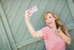 Flirty unga bärande hörlurar för vuxen kvinna som tar en Selfie med hennes Sma Arkivfoto