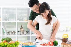 Flirty weekend. Flirty couple chopping vegetables for a weekend lunch Royalty Free Stock Image