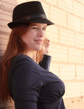 A Flirty Wink. Attractive red head woman in fedora hat winking Royalty Free Stock Photography
