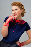 Flirty woman. Blonde girl in a dress flirts biting her finger Stock Image