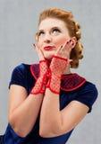 Flirty woman. Blonde girl in a dress flirts biting her finger Royalty Free Stock Photos