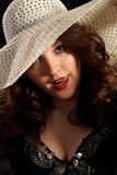 Flirty woman in a hat. Flirty young beautiful woman in a hat Royalty Free Stock Photography