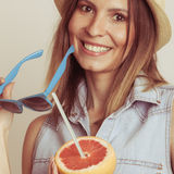 Flirty woman in hat hold sunglasses and grapefruit Stock Photos