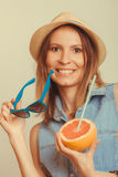 Flirty woman in hat hold sunglasses and grapefruit Royalty Free Stock Photography