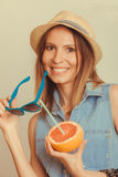 Flirty woman in hat hold sunglasses and grapefruit Stock Image