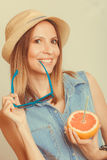 Flirty woman in hat hold sunglasses and grapefruit Royalty Free Stock Photo