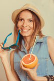 Flirty woman in hat hold sunglasses and grapefruit Stock Images