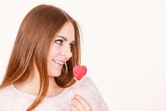 Flirty woman holding red wooden heart on stick Royalty Free Stock Photography