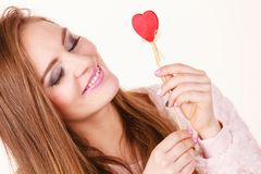 Flirty woman holding red wooden heart on stick. Romantic gestures, valentines gifts ideas concept. Happy flirty woman holding red wooden heart on stick stock photography