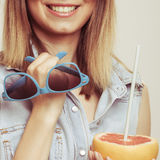 Flirty woman holding sunglasses and grapefruit Royalty Free Stock Photo