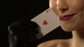 Flirty woman showing ace of hearts into camera, fortune concept, luxury casino. Stock footage stock video footage