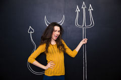 Flirty woman standing and winking over chalkboard background Stock Images
