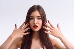 Flirty young woman caring of her appearance. Voluptuous girl is showing her manicure. She is raising hands to face and looking forward with sensuality. Lady has Royalty Free Stock Photos