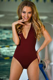 Flirty young woman model in elegant swimsuit posing indoor. Royalty Free Stock Photo