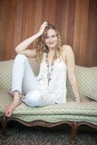 Flirting woman. A smiling young woman with feet up sitting on couch royalty free stock photo