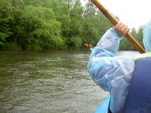Flisactwo na spokojnej rzece Paddle w ręce mężczyzna w błękitnym wodoodpornym żakiecie Fotografia Stock