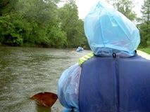 Flisactwo na spokojnej rzece Paddle w ręce mężczyzna w błękitnym wodoodpornym żakiecie Zdjęcie Royalty Free