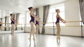 Flitiga flickor lär moment på tåspetsarnadans i balettstudio Startande balettdansörer är konstiga, dem är lager videofilmer