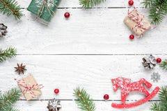Flitter in einem blauen Glas Rahmen gemacht von den Tannenzweigen, von den roten Beeren, vom Retro- Weihnachtsspielzeug, von den  Stockfotografie