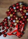 Flitter in einem blauen Glas Rot lackierte Schuhe mit Fersen und einem Kranz von Weihnachtsbällen, Draufsicht Stockbilder