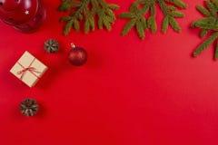 Flitter in einem blauen Glas Tannenbaumaste, Kiefernkegel Weihnachtsdekorationen und anwesende Geschenkboxen auf rotem Hintergrun stockbilder