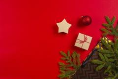 Flitter in einem blauen Glas Tannenbaumaste, Weihnachtsdekorationen und anwesende Tasche, Geschenkbox auf rotem Hintergrund stockbilder