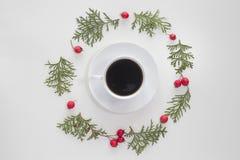 Flitter in einem blauen Glas Tasse Kaffee mit den grünen Thujazweigen und den roten wilden rosafarbenen Früchten auf weißem Hinte lizenzfreie stockfotografie