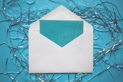 Flitter in einem blauen Glas Umschlag mit einer Karte Lamettadekorationen auf blauem Hintergrund Kopieren Sie Platz lizenzfreies stockfoto