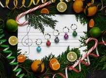 Flitter in einem blauen Glas Weihnachtsdekorationsbälle werden auf dem Papier wie Musikanmerkungen vereinbart Lizenzfreies Stockfoto