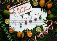 Flitter in einem blauen Glas Weihnachtsdekorationsbälle werden auf dem Papier wie Musikanmerkungen vereinbart Stockfotos