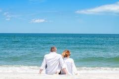 flitterwochen Glückliches Paar, das auf tropischem Strand sitzt stockfotos