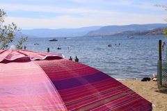 Flitterwochenkreuzfahrtregenschirm am Strandhalt Lizenzfreies Stockbild