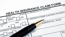 Füllen des Krankenversicherung-Antragsformulars Lizenzfreie Stockfotografie