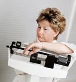 Fällige Frau auf Gewicht-Skala Stockfoto