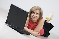 Fällige Frau, die auf hölzernem Fußboden unter Verwendung des Laptops liegt Stockbild