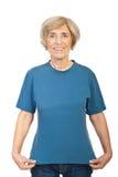 Fällige Frau, die ihr T-Shirt zeigt Stockbild