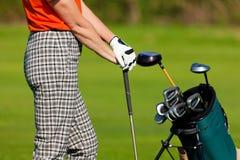 Fällige Frau mit dem Golfbeutel, der Golf spielt Stockfoto