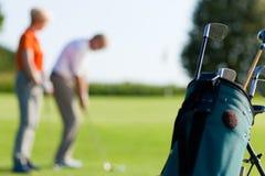 Fällige Paare, die Golf (Fokus, spielen auf Beutel) Stockfoto