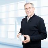 Fälliger Geschäftsmann, der eine Kaffeepause hat Stockfoto
