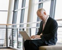 Fälliger Geschäftsmann, der an Laptop arbeitet Lizenzfreies Stockbild