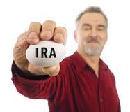 Fälliger Mann hält weißen Notgroschen mit IRA auf ihm an. Lizenzfreie Stockfotografie