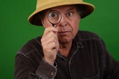 Fälliger Mann mit Vergrößerungsglas Stockbilder