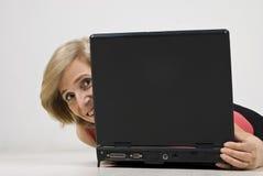 Fälliges Frauenfell hinter Laptop Stockfotografie