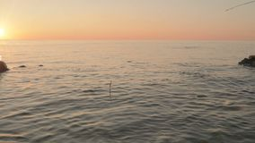 Float with a bird feather handmade floats in the sea. Slow motion stock video