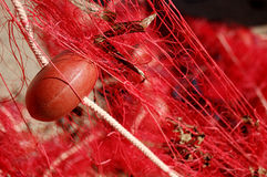 A float close up. A red and dirty fishing net with a float in foreground Royalty Free Stock Photography
