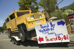 Float of a Hummer vehicle powered by vegetable oil with sign that reads Powered By Oil makes its way down main street during a Fou Stock Image