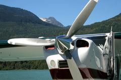 Float Plane. A float plane parked on a green glaciel lake in the mountains Royalty Free Stock Image
