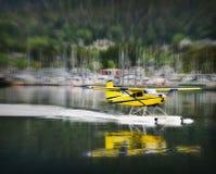 Float Plane Landing, Alaska. Yellow float plane landing on a water passage way in the island coastal community of Sitka, Alaska on the inside passage royalty free stock image