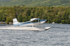 Float plane or seaplane taking off. Flying float plane or seaplane taking off at a lake Royalty Free Stock Images